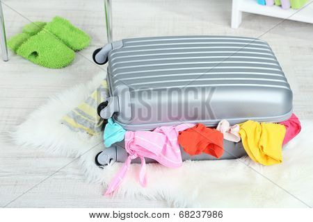 Suitcase with clothes on mat on room background
