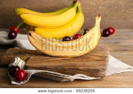 Halved and whole ripe bananas and cherries on wooden background