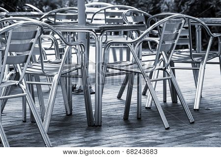 tables and chairs in a cafe on the street