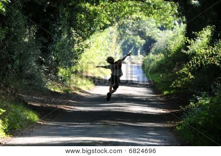 Child jumping for joy on a country lane in autumn