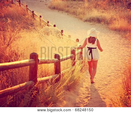 a woman walking on a path during sunset or sunrise toned with an instagram like filter