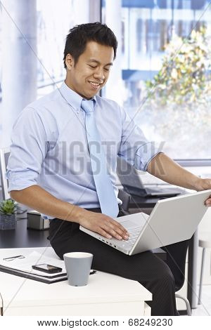 Businessman sitting on top of desk, using laptop computer in bright office.
