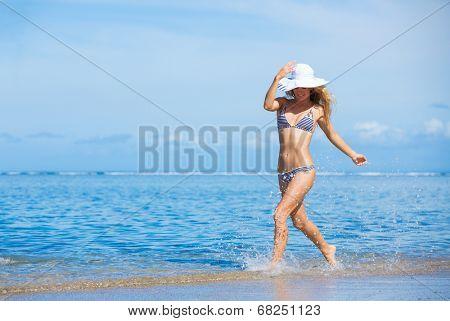 Happy beautiful woman enjoying sunny morning at the beach f