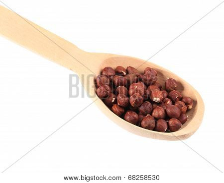 Wooden spoon with hazelnuts.