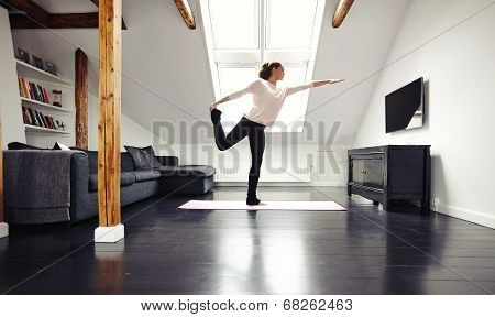Fit Young Lady Practicing Yoga At Home - Warrior Pose