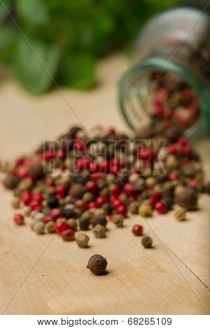 Heap Of Peppercorns On Top Of Wooden Table Before Glass Jar And Fresh Basilica.
