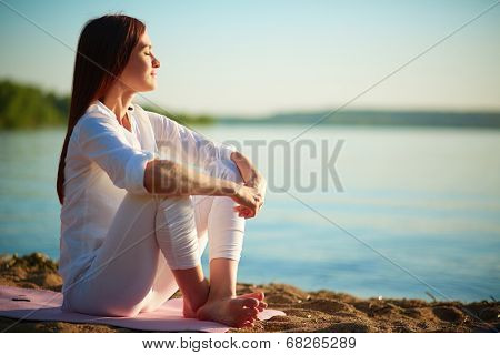 Side view of serene woman sitting on sandy beach against blue sky outdoors