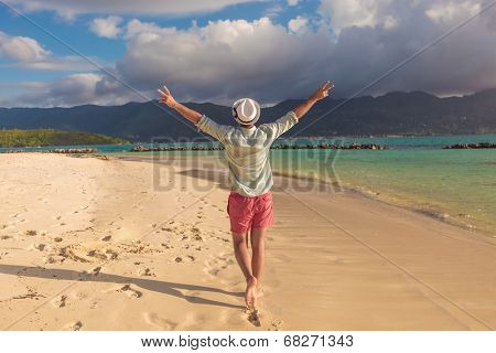 back of a sexy young man walking on the beach and celebrates his joyous life