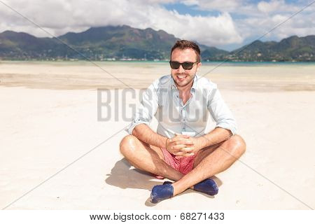 smiling young man with sunglasses sitting on a beach and looks to the camera