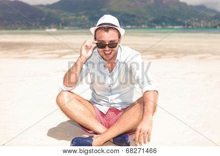 smiling seated young man taking off his sunglasses and looks happy to the camera