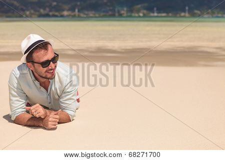 smiling young man with sunglasses and hat , lying on the beach and looks away