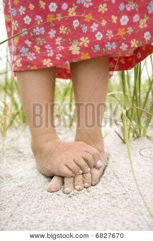 Pequeños pies de las niñas en la arena