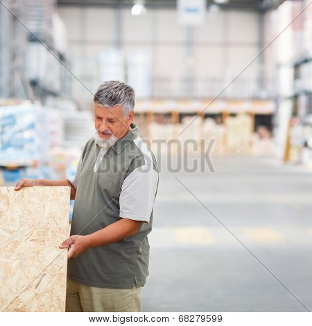 Man choosing and buying construction wood in a  DIY store for his DIY home re-modeling project