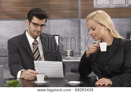 Young businesspeople having meeting in meetingroom, looking at papers, drinking coffee.
