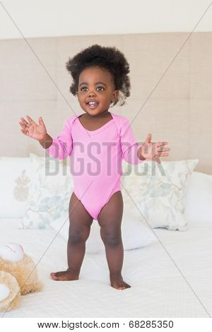 Baby girl in pink babygro standing on bed at home in the bedroom