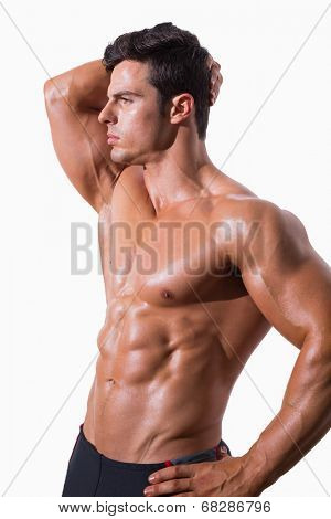 Young shirtless muscular man posing over white background