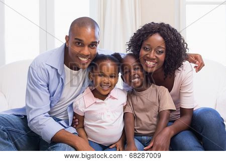 Happy family smiling at camera together at home in the living room