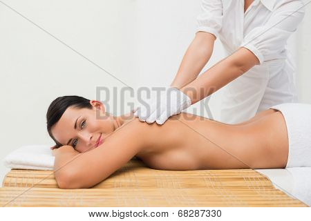 Beautiful brunette enjoying an exfoliating back massage in the health spa