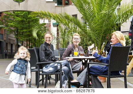A diverse group of women, enjoying some leisure time around a table at a terrace, with the daughter (out of focus) playing cheerfully. Candid shot with copy space on top of the image.