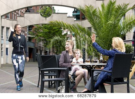 A group of three, very diverse women, meeting on a terrace. A sporty jogging woman waves at a senior lady, with a mother and her young daughter also sitting at the table in an urban setting.