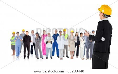 Composite image of smiling architect with hard hat against group of workers