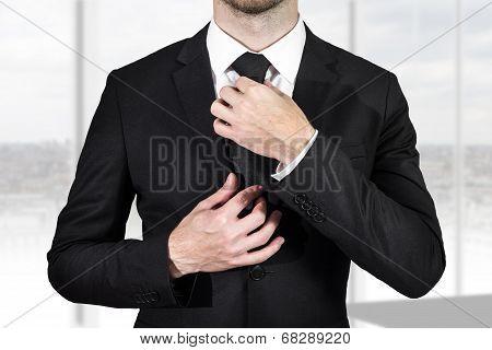 Businessman Correcting Necktie