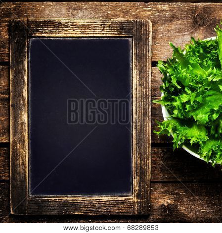 Black Chalkboard For Menu And Fresh Salad Over Wooden Background. Diet Food Restaurant And Healthy L