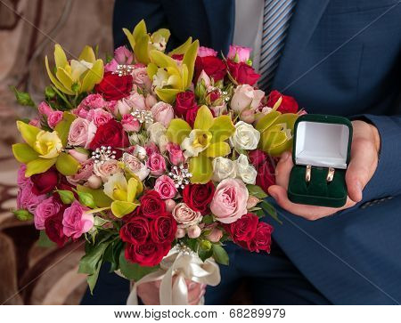 Bridal Bouquet And The Ring In The Hands Of The Groom