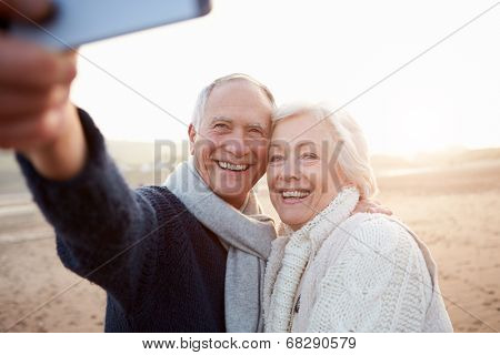 Senior Couple Standing On Beach Taking Selfie