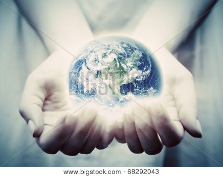 The earth shines in young woman hands. Concepts of save the world, protection, taking care, environment. Elements of this image furnished by NASA