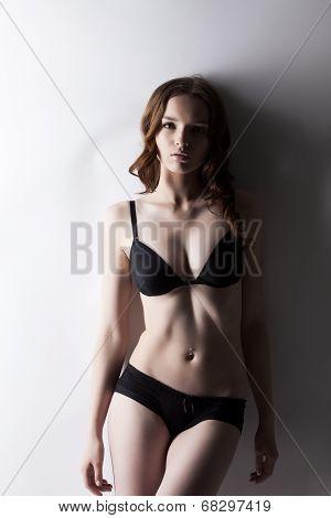 Beautiful girl like doll posing in black lingerie