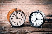 stock photo of analogy  - Beautiful old alarm clocks on the wooden floor - JPG