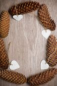 stock photo of sm  - Heart shaped Christmas decorations and spuce cones frame on wooden table. Merry Christmas. vertical photo. handmade ornaments. Empty wooden background in center of photo for your own text or message. greeting card.