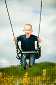 foto of swingset  - Little blonde boy having fun at the playground - JPG