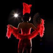 Burlesque dancer with red plumage and short dress, black background poster
