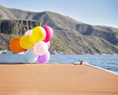 picture of dock a pond  - multicolored balloons tied to a dock on a windy day - JPG