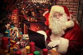 stock photo of letters to santa claus  - Santa Claus sitting at the table with a laptop at his home - JPG