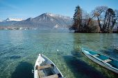 image of annecy  - View of Annecy lake from the city with small fishing boats island and snowed mountains. Savoy France in Europe