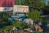 stock photo of derelict  - Old derelict truck on a country site overgrown with bushes - JPG