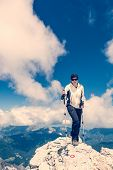 stock photo of ascending  - Female climber ascending a mountain top with trekking poles - JPG