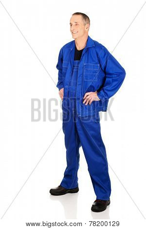 Full length smiling repairman with hands on hips.