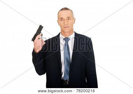 Portrait of serious mafia agent with handgun.