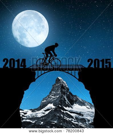 Cyclist riding across the bridge in night. In the background Matterhorn. Forward to the New Year 2015