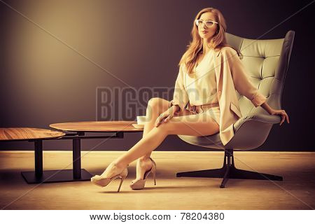 Portrait of a beautiful fashionable model sitting in a chair in Art Nouveau style. Interior, furniture.