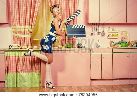Beautiful pin-up girl on a pink kitchen posing with cinema clapper board. Retro style. Show business. Cinematography.