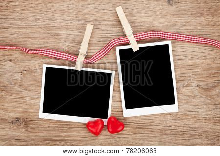 Two blank instant photos with candy hearts. On wooden background