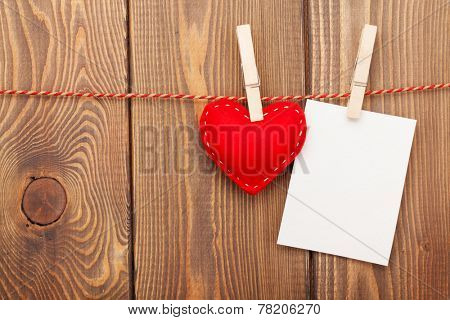 Photo frame and valentines toy heart over wooden background