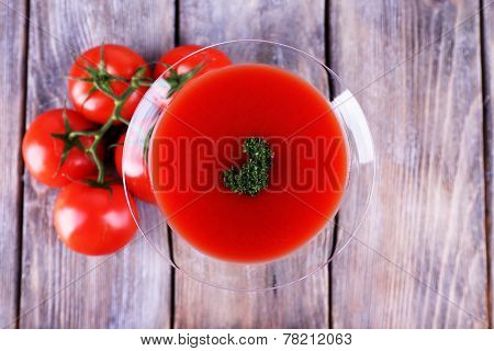 Tomato juice in goblet and fresh tomatoes on wooden background
