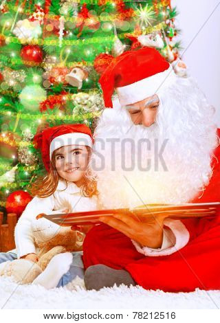 Happy Christmas eve at home, cute little baby girl sitting near beautiful xmas tree and reading magic book with Santa Claus, enjoying winter holidays