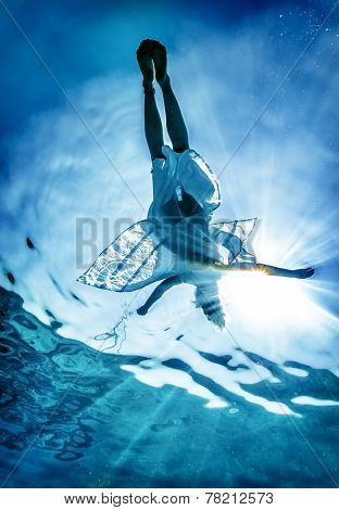 Woman's silhouette on sea surface, young female enjoying swimming underwater, spending summer vacation on beach resort, active lifestyle concept